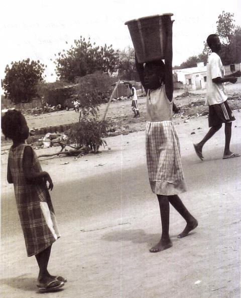 fille portant de l'eau pour sa famille d'acceuil