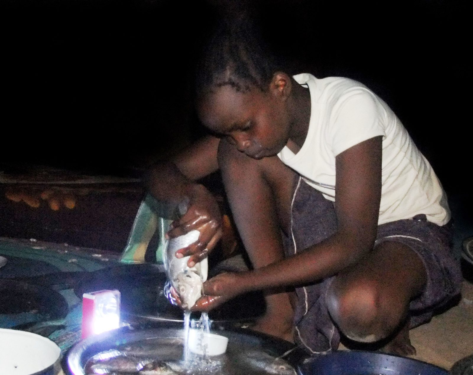 Fille, travaillant tard dans la nuit pour préparer le repas de sa famille d'acceuil